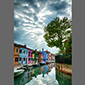 image of dramatic clouds, houes and canal, Burano, Italy